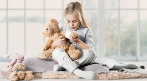 Blond girl blowing on LIVOPAN bear's arm.